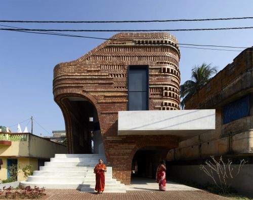 Varied Bricks and Ceramic Blocks Comprise the Asymmetric Facade of a Spacious Community Center in Bengal
