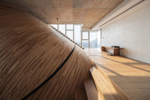 A Striking Curved Wall Swells Upward Across Three Stories of a Taipei Home by Yuan Architects