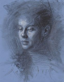 Portrait of a young man drawing on blue paper